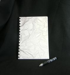 Logon and password notebook with a crumpled paper by GunnySack, $10.00