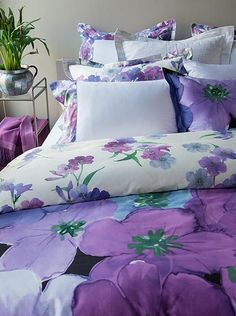 Bursting with brightly-hued flowers in shades of violet, lavender and blue, with emerald green leaves. The dark print features a black background and magnified blossoms, the light print has a crisp white background and smaller blossoms.  Via our storefront's selection of linens & bedding.