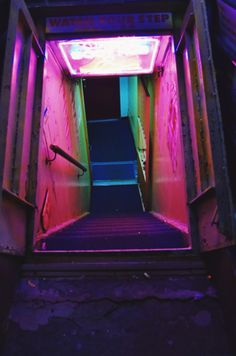 "image description: city stairwell leading down decorated with a ""watch your step"" sign and pink, purple, red, and green neon lights Vaporwave, Tableaux D'inspiration, Catty Noir, Neon Noir, Neon Aesthetic, Violet Aesthetic, Night Aesthetic, Nocturne, Neon Lighting"
