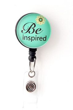"""This badge holder features an inspirational saying, """"Be Inspired"""" over an aqua blue backgroundID Badge reels are stylish and practical. They are a great accesso"""
