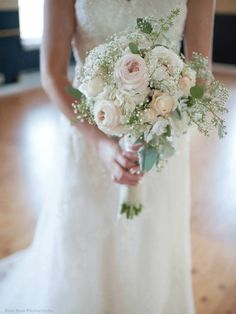 Bridal Bouquet featuring pink, blush, and ivory toned flowers. Very large ivory Hydrangeas were placed as the base, while Spray roses, Peonies, Baby's Breath, Vendella Roses, Dusty Miller, and seeded Eucalyptus were gently placed within the Hydrangea. The stems were wrapped in burlap and a cream satin ribbon was placed around the burlap which incorporated hand sewn vintage pearl buttons chosen by the bride.