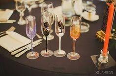 Set pahare miri personalizate, pictate manual in culori speciale pentru sticla.  Pahare de 160 ml, pictate cu profilul mirilor. Personalizarea s-a realizat in acord cu accesoriile purtate si in nuantele decoratiunilor florale si a salii: portocaliu si mov. Pe piciorul paharului sunt scrise numele mirilor, a nasilor si data evenimentului.