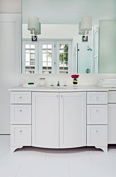 Custom bow-front vanity cabinet with sconces and wall mirror