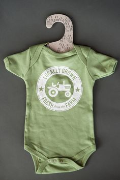 """Organic """"Locally Grown"""" Onesie for budding farming babies! Made in USA. Let's raise the next generation being more connected to wear their food comes from. Plus we feed 12 Americans in need per item sold!"""