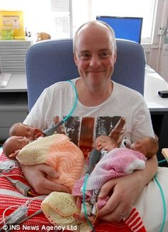 Proud dad: Smiling father Julian holds the two sets of identical twins - wow well done from www.twinsgiftcompany.co.uk