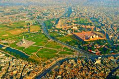 This is an aerial shot of Lahore city. Badshahi Mosque and Lahore Fort can be spotted on the right side and Minar-e-Pakistan inside Iqbal Park can be seen on the left.