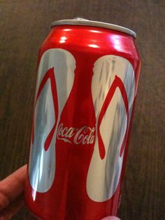 Coke can with 2 flip flops forming a Coke bottle in the middle.