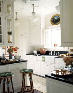 1930's lighting, Shaw apron sink, black countertops, french bistro barstools; interior design by Nancy Boszhardt