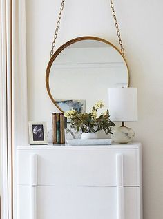 A crisp white dresser gets an antique accent with a vintage-style hanging brass mirror, alabaster table lamp and collection of books.