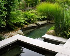 Stone is a key ingredient for a garden pond. But remember that plants can define the space as well. Asian style meets English garden flair in the water feature below. Note the use of lush plants and interesting greenery, such as grassy Miscanthus (second from the right)