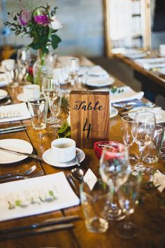 Stunning table design with deep red fruits and wildflowers in cut glass vases. Eucalyptus was strewn on the tables for a gorgeous look and smell at this industrial barn wedding by glass slipper weddings.