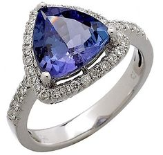 Fourteen karats of shimmering white gold play host to a magnificent tanzanite stone accented with 37 sparkling diamonds in this beautiful ring. Tanzanite Stone, Types Of Gemstones, Diamond Are A Girls Best Friend, Beautiful Rings, Frosting, Triangle, Dream Wedding, Objects, White Gold