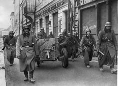 German infantrymen and artillerymen with 37-mm anti-tank gun PaK 35/36 advance in a Soviet city.