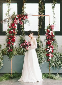 Long sleeve bridal gown and dreamy red botanical ceremony backdrop.
