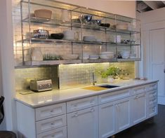 "Then there is ""la mattina,"" or the morning space – essentially a drop-dead-gorgeous breakfast bar with a wall covered by Ann Sacks Davlin subways made from white gold-leaf fused between handmade glass tiles. - Another view of an appliance garage."