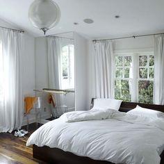 Lichtdurchflutete Schlafzimmer Amerikanischer Nussbaum Böden und dunklen Holzakzenten - wie das Bett mit seinen schrägen Kopfteil - heben diese all-weiß-Schema. Ein Ganzkörperspiegel funktioniert auch, um Licht durch den Raum reflektieren.