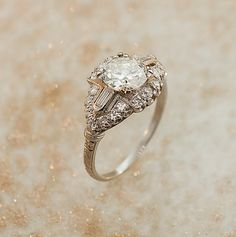 1930s Platinum & Diamond Engagement Ring: such a perfect example of 1930s glamour! This elegant ring has a 1.23 ct center diamond that is accompanied by side baguettes, and the setting glitters with small round diamonds all over it.
