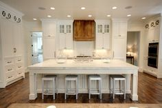 Not sure why, but audible gasp upon seeing this pic.  Of course, the white kitchen = lurve, but I don't care for the wood hood or stools. Do love the glass cabinets up high.