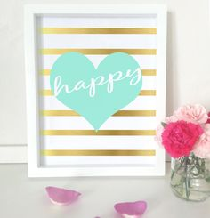 """This inspirational art print has the word """"Happy"""" in white against an aqua heart and striped gold foil effect background. This print is the"""