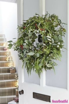 A welcoming Christmas entrance: Welcome guests with a handmade wreath. Press fir branches, crimson berries and eucalyptus into a loose arrangement for a relaxed effect. (Styling by Sally Cullen and photography by Mark Scott) #wreath #christmaswreath #christmas #christmasdecor #christmasdecoration #frontdoor #christmascraft