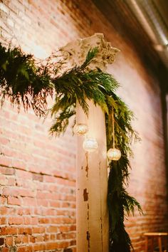 The ceremony site is framed with antique wood columns, glass globes with tea lights, and a garland of evergreens. Winter Boho Industrial Wedding at 1927 Events in Seattle | Ryan Flynn Photography