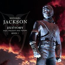 """A image of a silver statue that is wearing a military-like outfit and has its hair clipped behind its head. To the left of the statue the words """"MICHAEL JACKSON"""" are written in white letters and underneath those two words are other words written in smaller white print. Behind the statue, a sky with clouds that are black and red can be seen."""