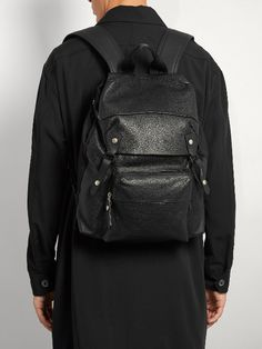 Lanvin's refined black grained-leather backpack is detailed with smooth leather panels, and accented with silver-tone metal hardware for a tough edge. Ultra-functional, it unfolds to reveal an internal drawstring top closure, and comes with three internal slip pockets and a single front zip pocket for optimum everyday organisation. The padded shoulder straps add further ease.