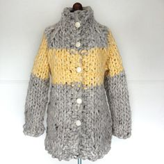 This one of a kind cardigan sweater/coat was hand-knit using giant handmade needles, enormous, thick wool yarn and detailed with reclaimed white leather buttons. The result is bold--and incredibly warm.