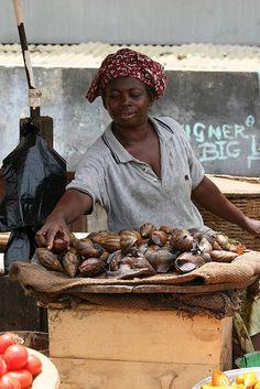 Pretty lady selling giant edible snails, Ghana.