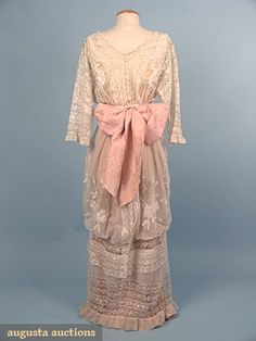 Hobble-style tea gown, circa 1913 (back.) One-piece dress fashioned from various laces including Val, torchon, and embroidered net. The skirt panels are embroidered with flower baskets. Wide pink brocade silk sash.