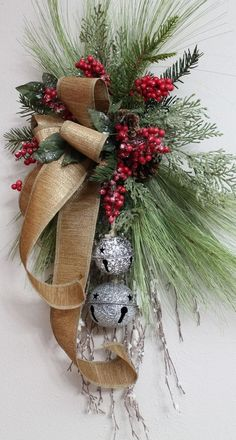 An arfully designed door swag by Exclusively Christmas with long needle pine, glittered cedar sprays, red holly berries and a glittered iced snow branch all combined together to showcase a set of rustic metal bells and a streaming gold wired ribbon. Christmas Swags, Noel Christmas, Country Christmas, Holiday Wreaths, Christmas Crafts, Christmas Ornaments, Burlap Christmas, Primitive Christmas, Christmas Door Wreaths