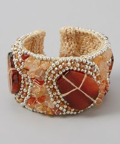 Far from ordinary, this handmade cuff is made from woven silk thread topped by a beautiful array of wrapped glass stones for a look that's guaranteed to get noticed.