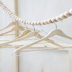 De grosses perles de bois sur un fil pour suspendre des cintres pour la tenue du lendemain. Dans un coin de dressing ou de la chambre d'enfant ?