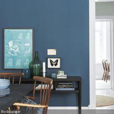 Vor dem Hintergrund der blauen Wandfarbe bekommen Wanddeko und Möbel besondere Aufmerksamkeit. Helle Wandbilder machen sich als Kontrast zur dunklen Farbe gut – …