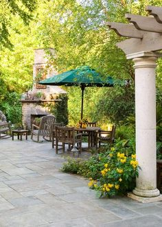 Multiple seating areas arranged for casual conversation around the fireplace or under the protection of an umbrella which can add a sense of enclosure in an open space. An outdoor fireplace can double as a wall for the outdoor room. A sturdy concrete column supports the beams of a pergola, and lends balance to the brick fireplace.