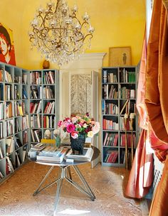 A narrow yellow library filled with books, crystal chandelier, and vase of flowers // Italian design
