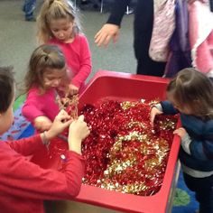 Celebrating Chinese New Year with a sand table bin of gold and red tinsel. Using chopsticks the children picked out a golden dragon and gold coin to take home.