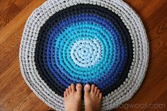 """Crochet this rug from 15 XXL men's t shirts. Cut the shirt horizontally beneath the arm holes and then cut into strips about 1"""" wide. They'll curl - that's good!. Wind into """"yarn balls"""" so you can alternate colors. When you're done, weave in the ends. Pick fabrics that are the same weight and makeup. 100% cotton works well."""