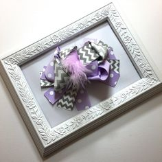 Our customers who like a more dramatic look will love this bow. Each bow includes grey chevron printed ribbon, purple polka dot ribbon and a purple marabou puff center. Each includes a sturdy alligator clip backing to secure this bow to your little ones hair or a headband. This bow is about 5.5 across, keep in mind that it sticks up quite a bit due to all the loopy ribbon and fluffy marabou. Please allow 3-5 business days for order to be shipped out.  All of my accessories come…