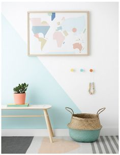 Beautiful pastel nursery with mint triangle detailing on the wall, a pretty geometric world map, plant and pastel and light grey carpet.