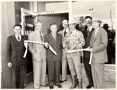 Judge Julian Beck (center) holding ribbon with members of the Reseda Chamber of Commerce as honorary mayor Montie Montana cuts it at the grand opening of a real estate office at 7115 Reseda Boulevard, circa 1950s. Reseda Chamber of Commerce Collection. San Fernando Valley History Digital Library.