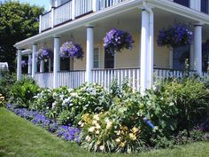 Love the house, the purple hanging baskets are perfect with the landscaping.  Great Porch, also. #FarmhouseLandscape