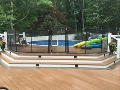 Above ground pool with deck and safety fence.