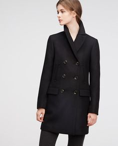 "Confident and sophisticated, our luxuriously crafted wool blend coat is one of fall's perfect pieces in a clean, streamlined silhouette. Stand collar with notched lapel. Long sleeves. Double breasted button front. Vertical besom chest pockets. Front flap besom pockets. Lined. 34"" long."