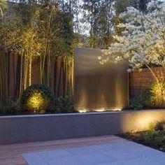 garden Seat planters and outdoor fireplace. with garden lighting. jardin Feng Shui avec terrasse en bois, projecteurs et bambou