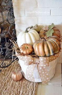 And speaking of paint, there is no harm in spraying a little glam to give new life to your gourds and pumpkins.  White silver, gold, or copper if you are tired of the orange, this is a simple way to swap up a look. This great little basket sitting on the hearth can balance out your decor if your mantel is a little top heavy.