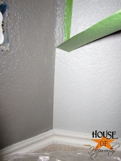 """So THAT'S the secret!!   Once you have your wall taped off, you will paint down the edge of the tape with your first color (light gray). This """"seals"""" the tape. Any paint that's going to bleed under the tape will be this 1st color, which is the same color as your newly painted wall, so when it bleeds, it will blend in."""