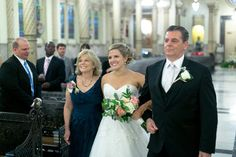bride smiles as she walks down the aisle with mom and dad