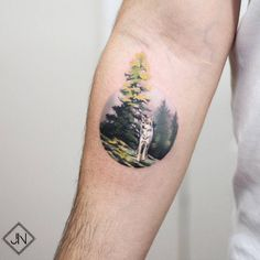 Wolf in the forest tattoo on the inner forearm.