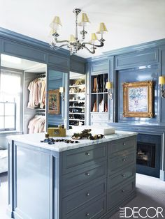 A baby blue walk in closet with an island bar, fireplace, and art-adorned mantel